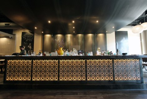 The soft glow of the bar. The wall behind the bar is covered with steel sheets. The color variation is a result of the steel's manufacturing process.