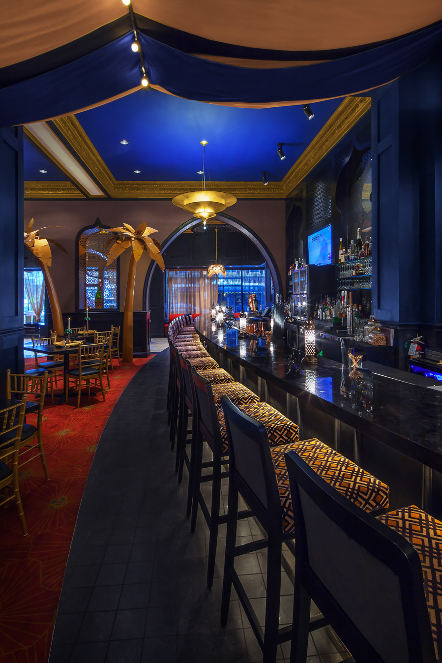 Black tile surrounds the bar, and a custom carpet that uses the colors from the Fox Theatre's carpet creates the dining area.