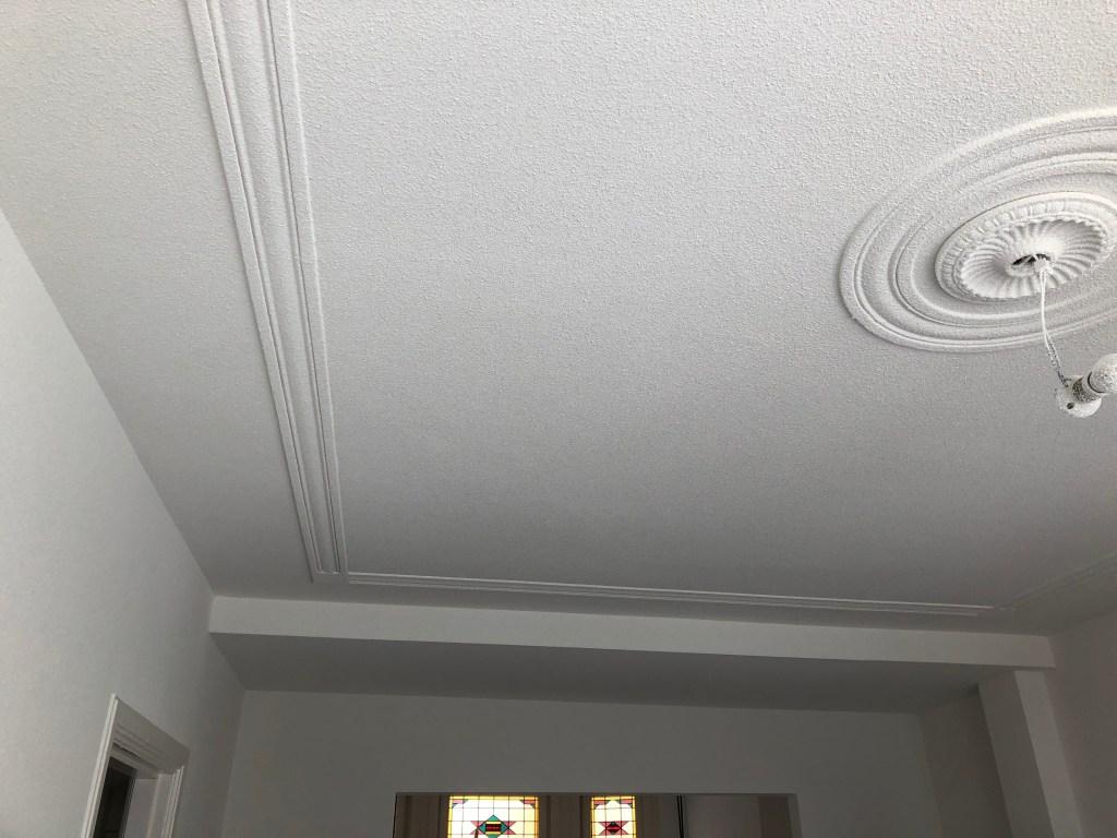 Plafond met ornament na herstelwerk + spackspuiten.