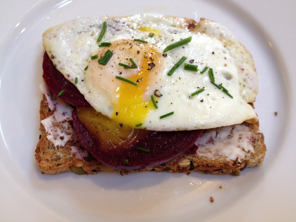 Pickled beets on toast with a fried egg and chives