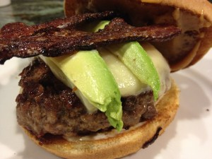 Hamburger with beer candied bacon, avocado and cheese