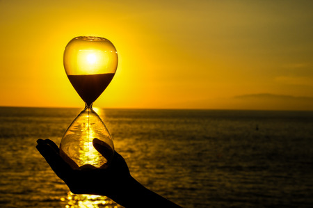 Image of a hand holding an hour glass backlight by the setting sun shining through the hourglass and reflecting on the ocean behind the hand.