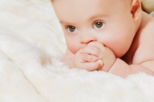 beautiful baby with Down syndrome on a white blanket