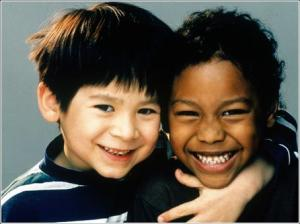 two kindergarten-aged boys hugging and smiling at the camera
