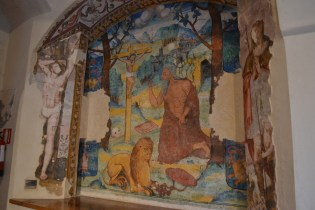 Fresco with a bearded lion at the foot of the Cross at the San Isidoro del Campo
