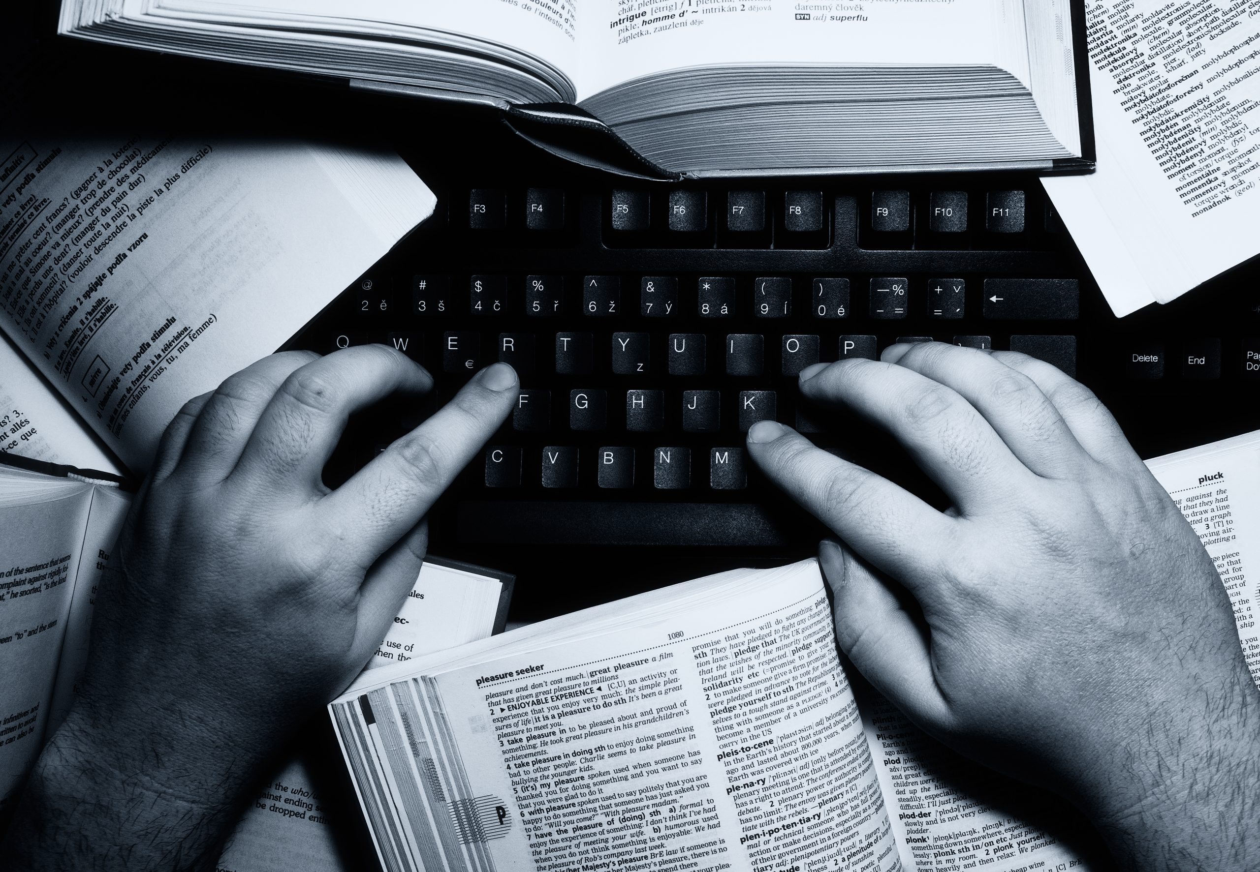 Closeup of man's hands typing on computer with dictionaries nearby