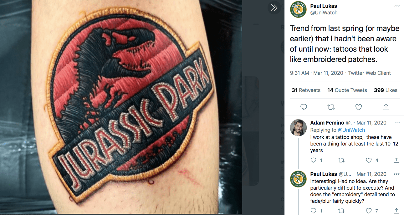 A tattoo of the Jurassic Park logo that looks like an embroidered patch, from twitter user Paul Lukas @UniWatch