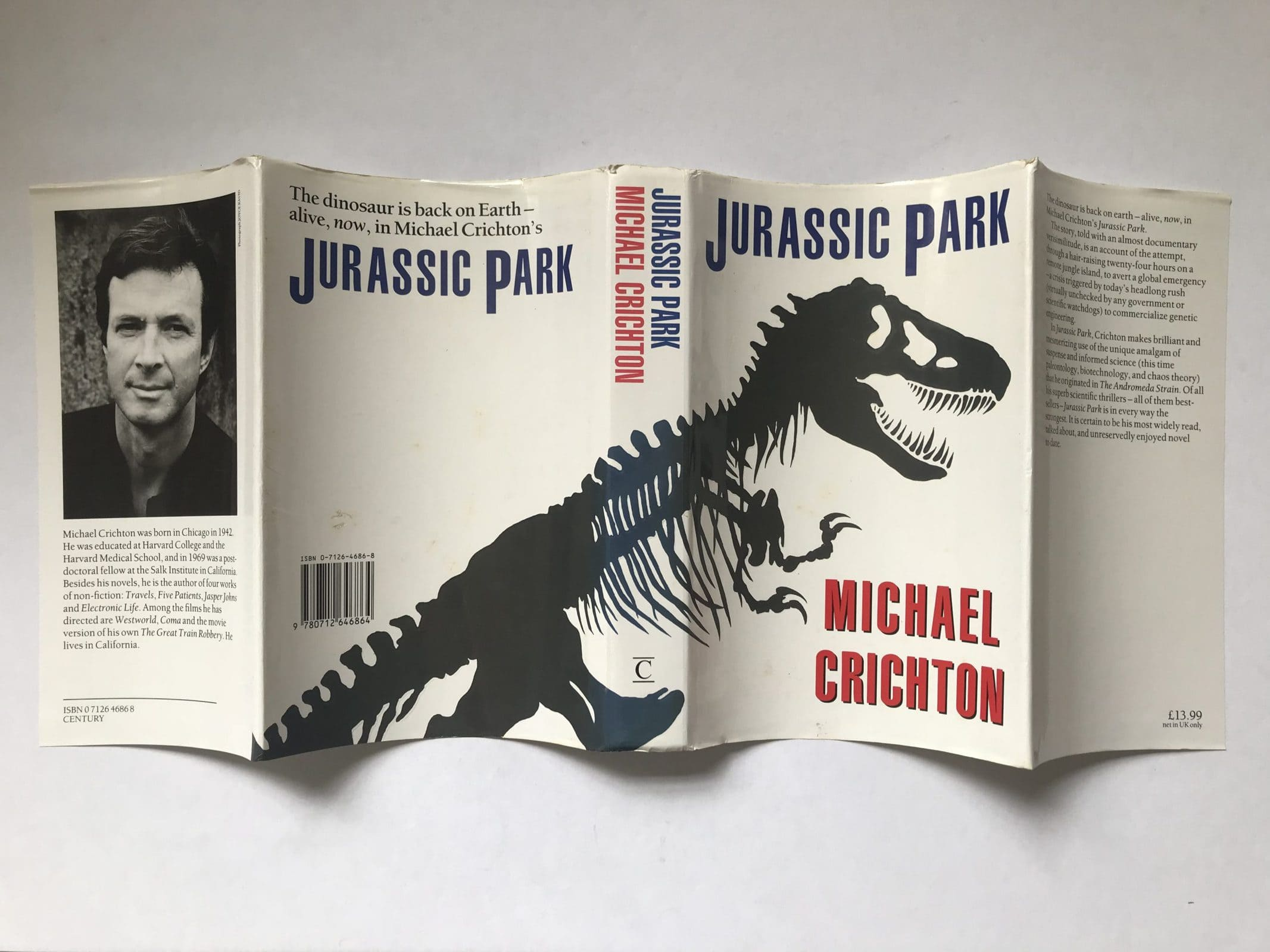 This book jacket from the first UK edition of Jurassic Park shows how the T. rex skeleton body wraps across the back and front of the book, while carefully avoiding placing his pelvis on the front cover. It also shows how the original dinosaur drawing was a very dark green. This edition is listed by John Atkinson Fine & Rare Books (and at time of posting is still available).