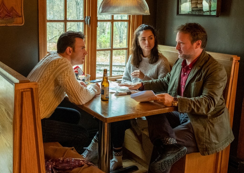 Talking through a script while on set in Berlin, Mass., director Rian Johnson, at far right, explores a scene with actors Chris Evans, left, in sweater, and Ana de Armas. Photo: Claire Folger/Lionsgate