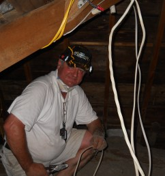 electrical contractor works in the hot summer attic [ 4000 x 3000 Pixel ]