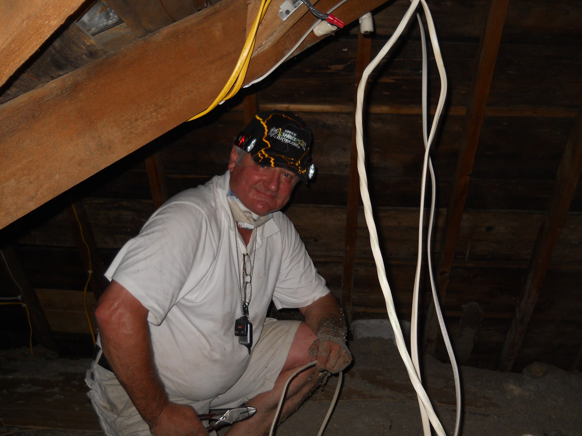 hight resolution of electrical contractor works in the hot summer attic
