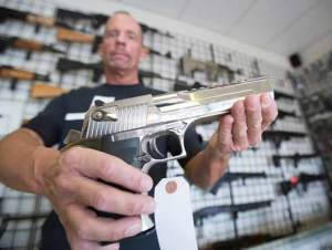 John Byrne/Tribune Kevin Marriott of Juggernaut Arms, a Sparks gun shop, displays a semi-automatic handgun in the store's newly expanded showroom.