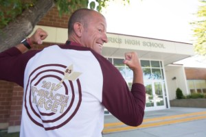 John Byrne/Tribune - Sparks High School Principal Kevin Conners points to the back of his shirt that displays the goal of the school year, to graduate all 85 seniors. The motivational shirts could be seen throughout the classrooms Monday morning as they were worn by the teaching staff on the first day of the new school year.