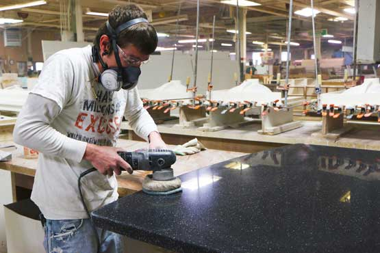 Young man sanding a Meganite Solid Surface Top
