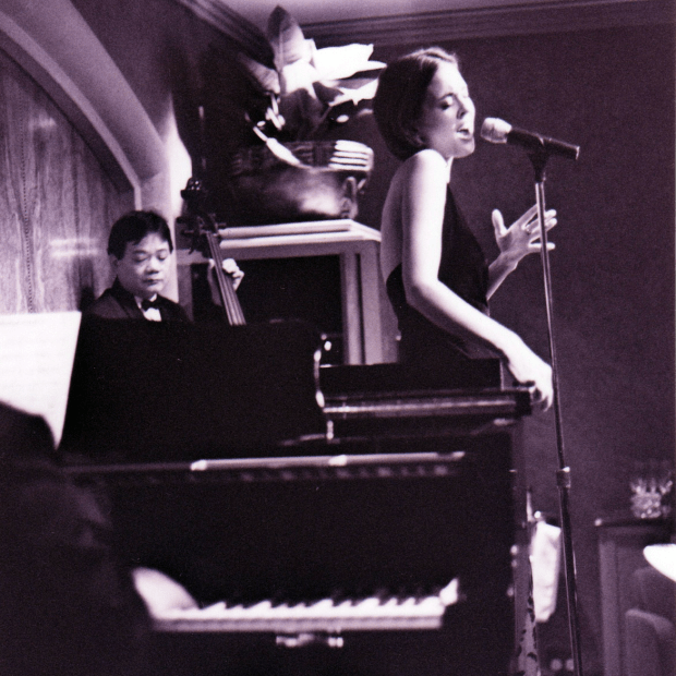 This black and white image shows the bass player's on the left in the background. Stephanie with short dark blonde hair, sings on the right and the piano keyboard in the left foreground. They're on stage in a glamorous Hong Kong cocktail bar.