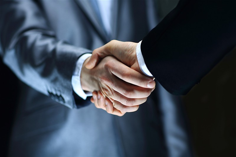 two business men shaking hands in a negotiation
