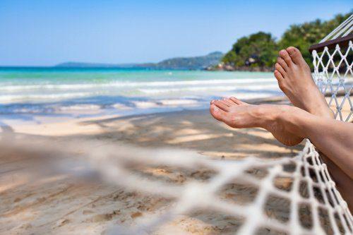woman feet in hammock on beach