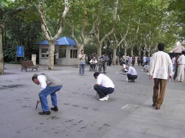 Shanghai: men writing in park
