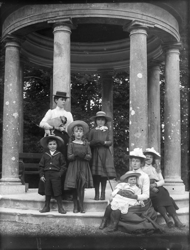 black-and-white glass-plate negative of women and children and a dog, posing on the grounds of Dromoland Castle