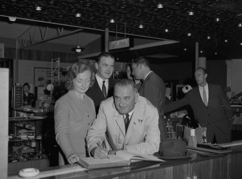 Lyndon B. Johnson signing Visitors Book in Shannon Airport gift shop [P50/1/1/3577 (SDN_LF_3675)]