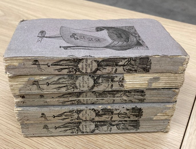 five books with cover illustrations of ships