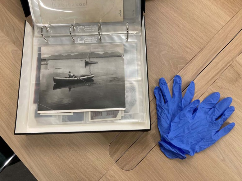 Examine photographs in the clear sleeves provided, or wear nitrile gloves and carefully handle loose photographs by their edges