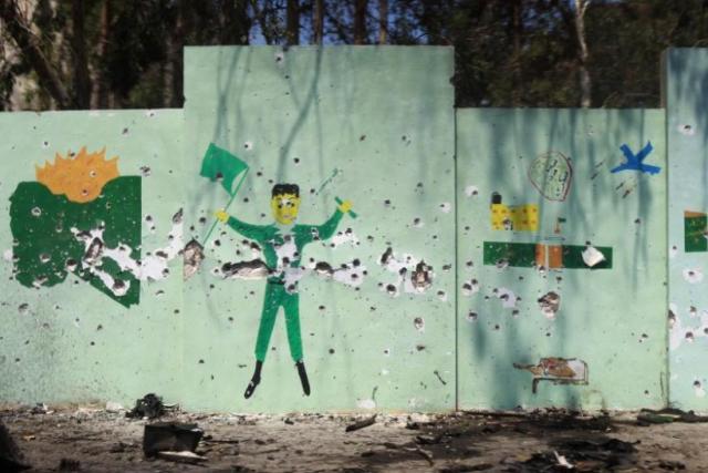 149188-a-wall-mural-depicting-gaddafi-government-propaganda-is-pocked-with-bu