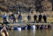 Manifestanti contro il Dakota Access Pipeline immersi nell'acqua fino alla vita davanti alla polizia, in un tentativo di attraversare n torrente per raggiungere dei terreni di proprietà della società che sta costruendo l'acquedotto, il 2 novembre 2016. (AP Photo/John L. Mone, File)