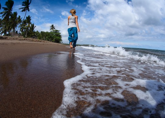 Young lady walking on a wet sandy beach