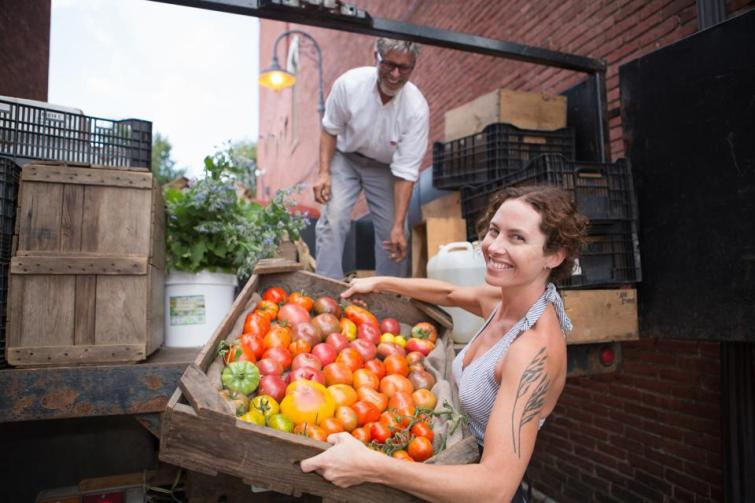 Farmers unloading crates of organic tomatoes outside grocery store