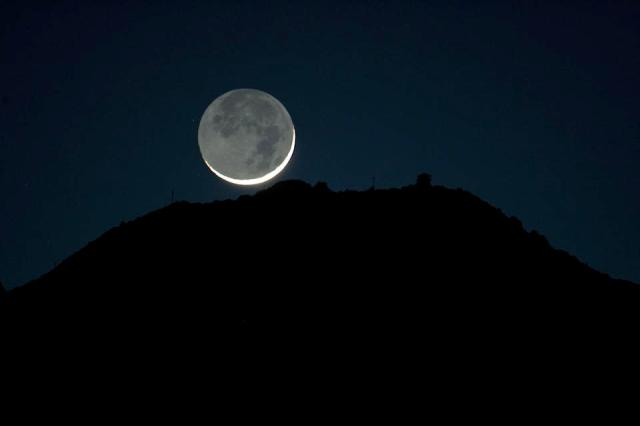 The crescent moon seen from Mill Valley set behind Mount Tamalpais Monday evening as rain clouds from the recent storm made way for a celestial show of earthshine where the earth reflects light from the sun back to the moon. (Photo by Frederic Larson/San Francisco Chronicle via Getty Images)