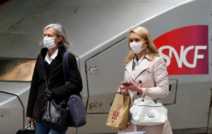 Passengers wearing protective masks pass a TGV (high-speed train) at Gare Montparnasse in Paris