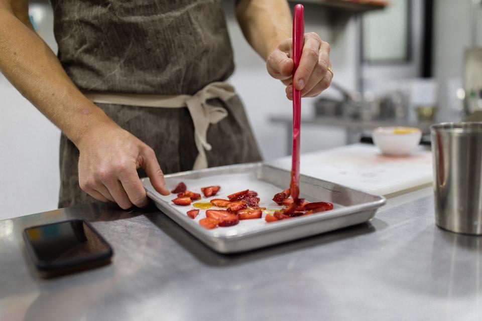 Tyler Malek prepping strawberries for ice cream.