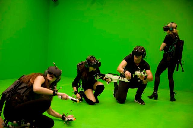 People playing in VR against a green screen