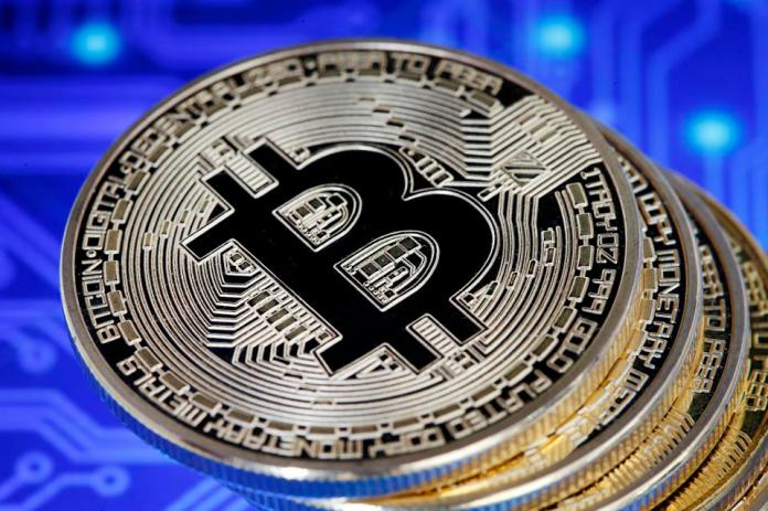 Bitcoin, a digital currency, stacked on top of a circuit board.