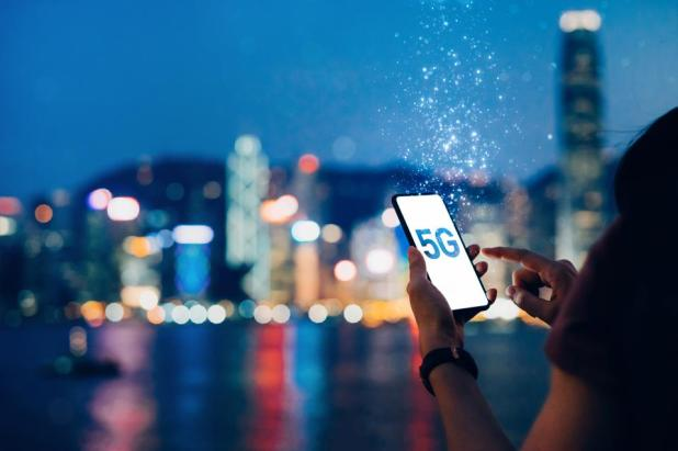 Cloud Computing: Young woman using smartphone against the iconic city skyline of Hong Kong by the promenade of Victoria Harbour at night, with the concept of 5G communications dissolved into light particles