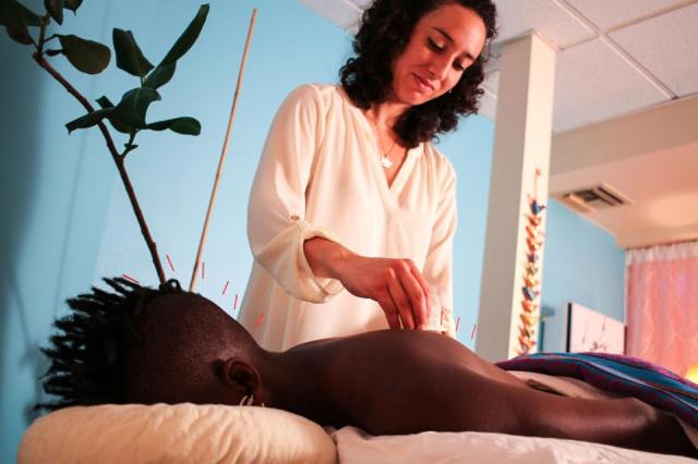 Adrianna Locke, LAc, performing acupuncture treatment on a patient