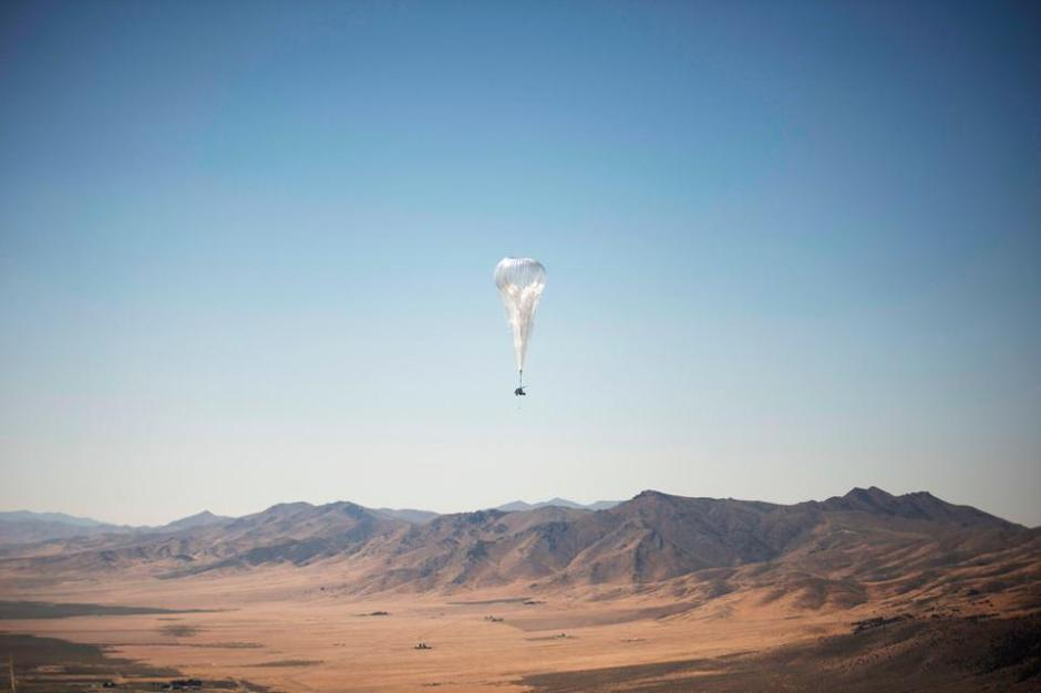 A high-altitude balloon in a blue sky over desert