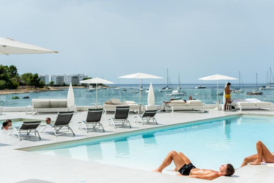 The pool and pool deck at AxelBeach Ibiza LGBTQ+ hotel overlooking San Antonio Bay.