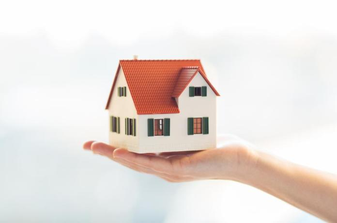 close up of hands holding house or home model