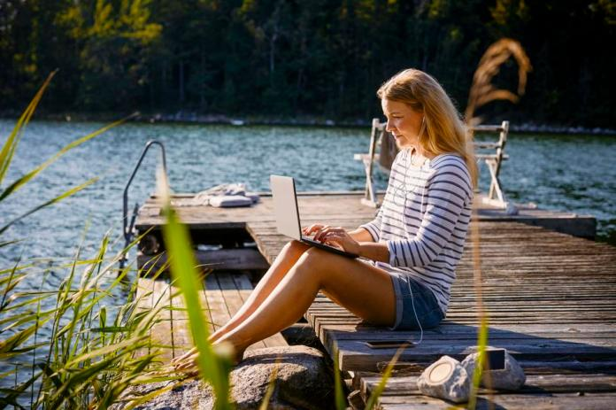 Woman with headphones using laptop while sitting on jetty against lake