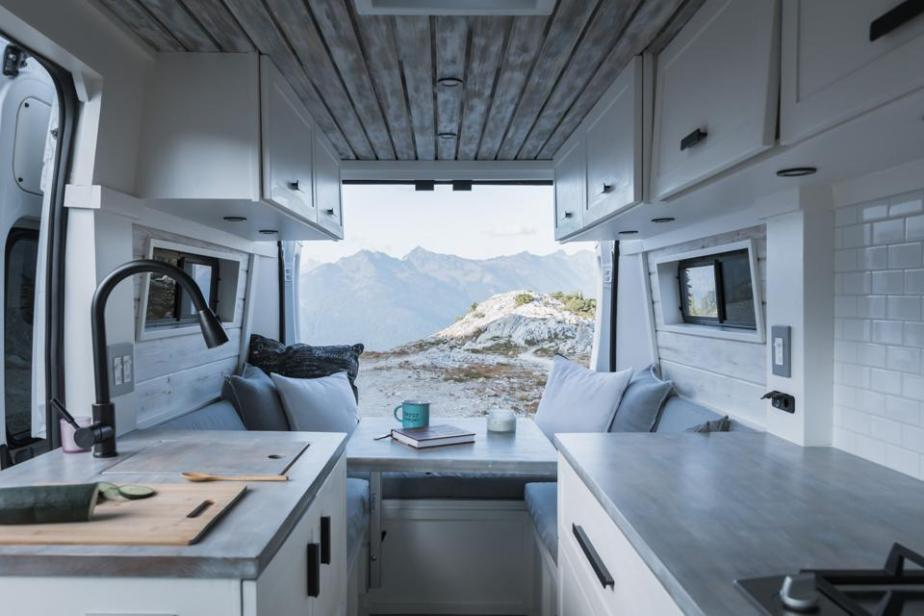 View of rugged mountains from a custom van with a kitchen and dining table.
