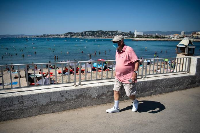 A man wearing a face mask walks along the beach ″ Pointe Rouge ″ Marseille France