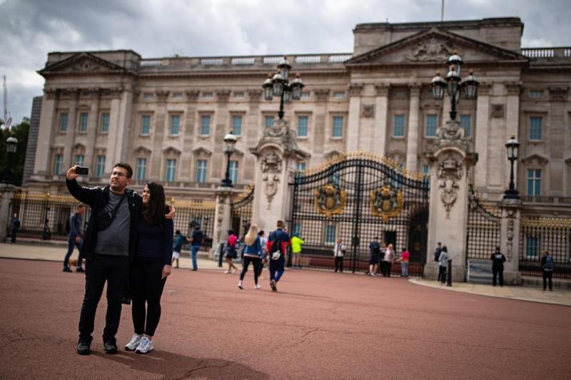 Tourists pose outside Buckingham Palace