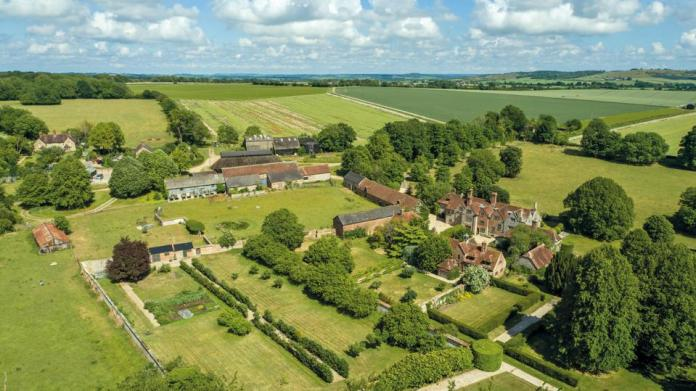 The house is surrounded by rolling countryside and farmland