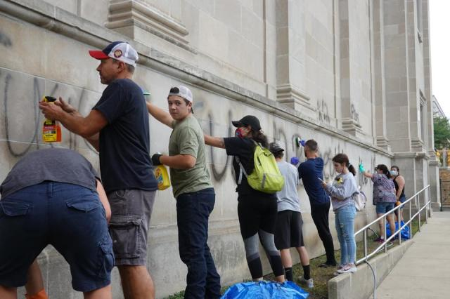 Kyle Rittenhouse (in green) was among the volunteers to clean graffiti from a high school near the Kenosha County Courthouse following a night of unrest on August 25, 2020 in Kenosha, Wisconsin.