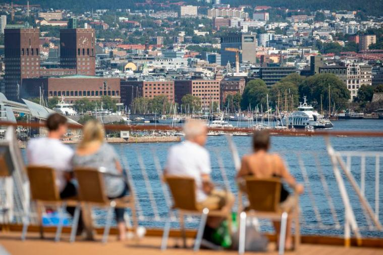 Norwegian people sit by lake in Oslo amid Covid EU  travel bans no travel in Europe