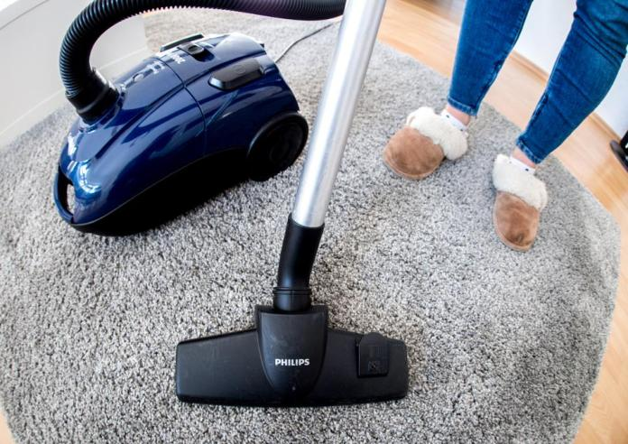 woman in an apartment is vacuuming a carpet with a Philips vacuum cleaner (shot with a fisheye lens).