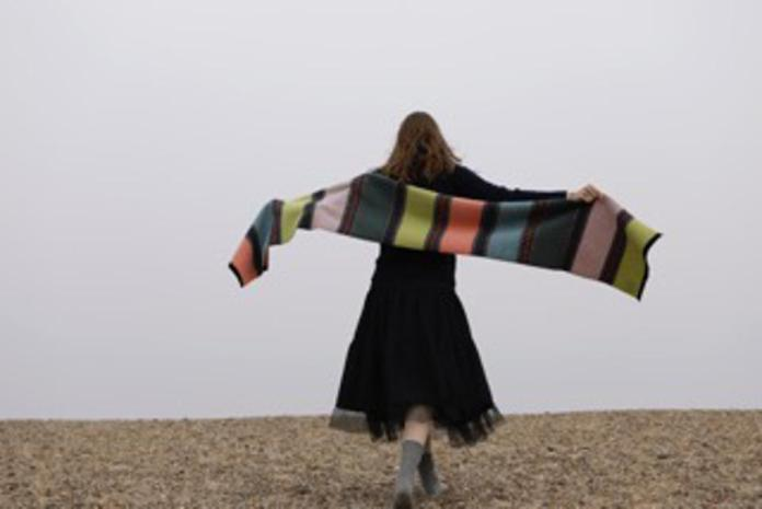 Woman on a beach with a woollen scarf