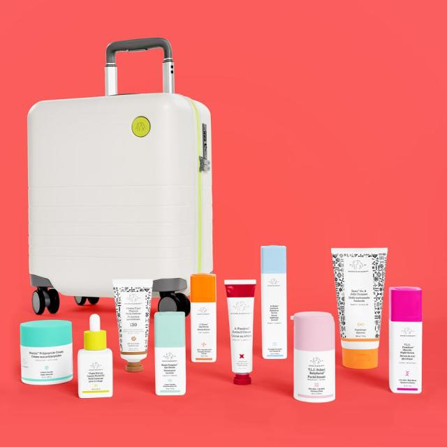 Drunk elephant products lined up in front of white Monos suitcase